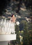 Sidosikt av en kvinna som läser en bok i en balkong Royaltyfri Foto
