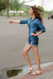 Sidosikt av en kvinna som liftar på stadsvägen royaltyfri fotografi