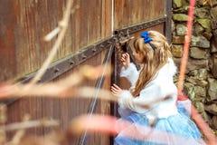 Sidosikt av en liten härlig flicka i landskapet av Alice i underland som ser in i nyckelhålet av porten Arkivbilder