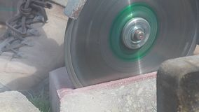 Sidosikt av en man som utomhus använder en vinkelmolar eller cirkelsåg för att klippa till och med ett kvarter lager videofilmer