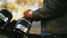 Sidosikt av en oigenkännlig motorcyklist som tar bruna läderhandskar och bär speciala läderkardor för att rida in arkivfilmer