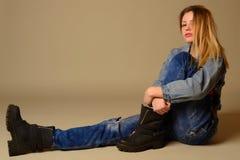 Sidosikt av en tillfällig ung kvinna som lägger på golvet arkivbilder