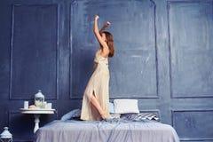 Sidosikt av en ung kvinna i en lång nattlinnedans på vara fotografering för bildbyråer