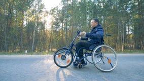 Sidosikt av en utbildningsrullstol som får rörd vid en rörelsehindrad person med hans armar arkivfilmer