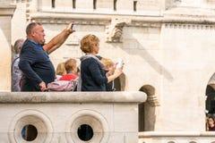 Sidosikt av ett caucasian turist- anseende för man och för kvinnlig på en synvinkel utanför och nedanför Matthias Church i Budape Fotografering för Bildbyråer