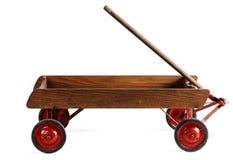 Sidosikt av ett gammalt barns trävagn som isoleras på vit Arkivbild