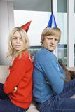 Sidosikt av förargade par i jultröjor och partihattar som tillbaka sitter för att dra tillbaka hemma Royaltyfria Foton