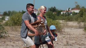 Sidosikt av familjen som går på till stranden lager videofilmer