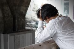 Sidosikt av frustrerad stressad ung asiatisk känsla för affärsman som svikas eller som är allvarlig med jobb fotografering för bildbyråer