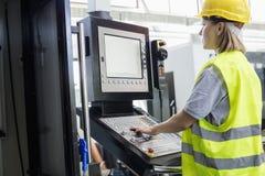 Sidosikt av fungerande maskineri för kvinnlig arbetare på kontrollbordet i fabrik fotografering för bildbyråer