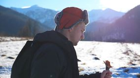 Sidosikt av gående nordiskt gå för ung fotvandrare med pinnar på snöig slinga i fält på bergbakgrund Sportig grabb lager videofilmer