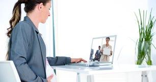 Sidosikt av gravid affärskvinnavideoconferencing i regeringsställning arkivbild