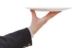 Sidosikt av handen med den tomma plana vita plattan Royaltyfri Bild