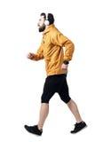 Sidosikt av idrottsman nen som joggar med hörlurar som bär omslaget royaltyfria foton