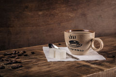 Sidosikt av koppen kaffe med en sked på en servett och kaffebönor Fotografering för Bildbyråer