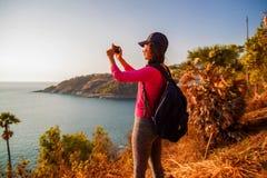 Sidosikt av kvinnan med ryggsäcken och smartphonen som tar fotoet på havet på kullen mot himmel arkivfoton