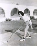 Sidosikt av kvinnan som spelar shuffleboarden arkivfoton