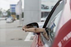 Sidosikt av kvinnasammanträde inom en bil och att se ut ur fönstret arkivfoto