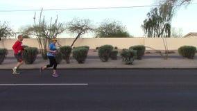Sidosikt av löpare som deltar i en maraton arkivfilmer