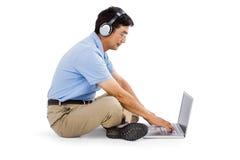Sidosikt av lyssnande musik för man, medan genom att använda bärbara datorn arkivbild