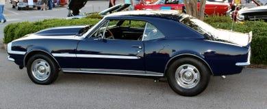 Sidosikt av mörker - blåa antika Chevy Camaro arkivfoto