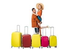 sidosikt av maninnehavflickvännen på händer med resväskor omkring arkivbilder