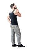 Sidosikt av mannen i ärmlös tröja och sweatpants som ser upp med handen på hakan royaltyfri bild