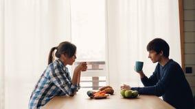Sidosikt av mannen och kvinnan som dricker te och talar sammanträde på tabellen i kök som tycker om tillsammans fridsam morgon på lager videofilmer
