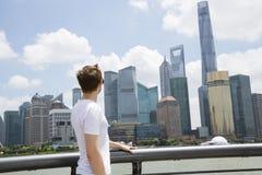 Sidosikt av mannen som ser den finansiella mitten för Shanghai värld mot molnig himmel royaltyfri foto