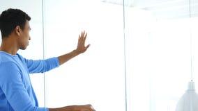 Sidosikt av mannen som ser till och med kontoret, händer på kontorsglasväggen Royaltyfri Bild