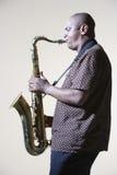 Sidosikt av mannen som spelar saxofonen Royaltyfri Bild