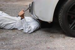 Sidosikt av mekanikern i den vita likformign som ner ligger och fixar under bilen Service för auto reparation arkivfoto
