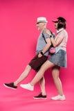 Sidosikt av moderiktiga höga par som poserar med ben upp på studion Royaltyfria Bilder