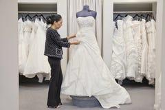 Sidosikt av mogen anställd som justerar den eleganta bröllopsklänningen i brud- lager arkivbild