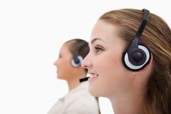 Sidosikt av operatörer som använder hörlurar med mikrofon Arkivbild
