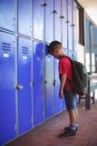 Sidosikt av pojkebenägenheten på skåp i korridor arkivbilder