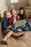 Sidosikt av pojken och flickor som använder den digitala bärbara datorn Royaltyfri Bild