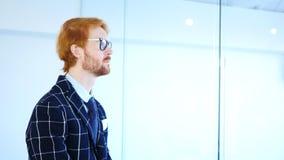 Sidosikt av rödhårig manaffärsmannen i exponeringsglas som ser till och med kontorsfönster Royaltyfria Bilder