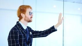 Sidosikt av rödhårig manaffärsmannen Looking till och med kontoret, händer på kontorsglasväggen Royaltyfria Foton