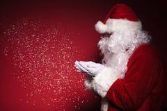 Sidosikt av Santa Claus som blåser snö Arkivbild