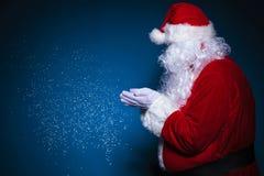 Sidosikt av Santa Claus som blåser snö Arkivfoto