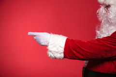 Sidosikt av Santa Claus som pekar hans finger till något Arkivbilder
