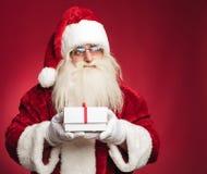 Sidosikt av Santa Claus som rymmer en närvarande ask Royaltyfria Foton