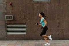 Sidosikt av sportig spring för ung kvinna på en trottoar royaltyfri foto
