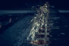 Sidosikt av springbrunnar för en rad som skiner i natten Natt i th royaltyfria foton