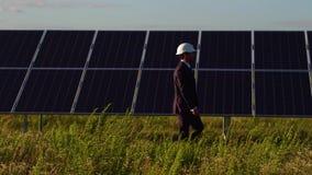 Sidosikt av stationsdirektören för sol- energi som går och kontrollerar photovoltaic paneler lager videofilmer