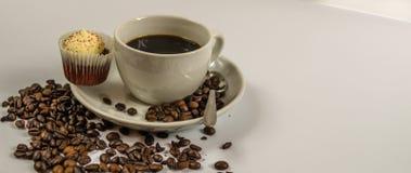 Sidosikt av svart kaffe i en vit kopp med den kräm- muffin, spil Arkivbilder