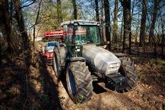 Sidosikt av traktoren på stora hjul på jordvägen i skog Fotografering för Bildbyråer