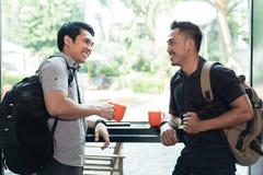 Sidosikt av två gladlynta unga män som talar och dricker kaffe royaltyfri foto