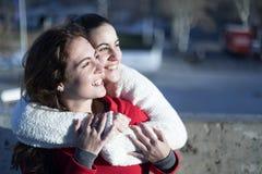 Sidosikt av två lyckliga kvinnor som bort omfamnar och ser parlesbisk kvinna den blåa homosexuell person för hjärtor för hjärta f royaltyfria bilder